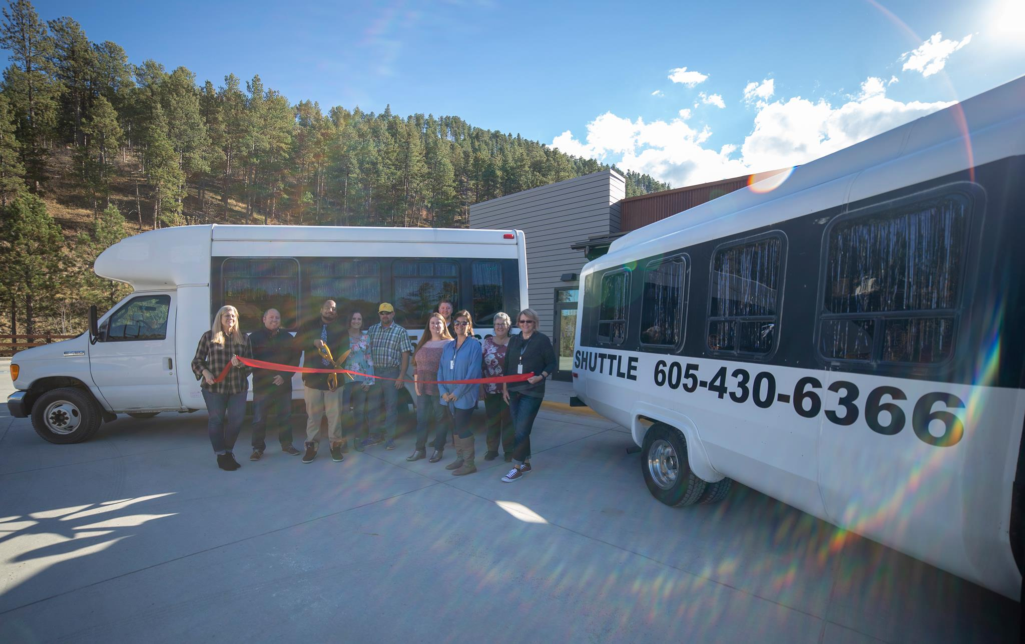 Another picture of the same group of ten people standing proudly in front of one of the shuttles during the ribbon cutting ceremony, including the driver - Jordan, and the owner - Stacey Phillips.